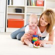 Baby playing with toys with happy mother — Stock Photo #3817140