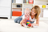 Baby playing with toys with happy mother — Stock Photo