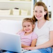 Woman with daughter with laptop — Stock Photo