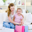 Mother with daughter with shopping bags at home — Stock Photo #3830605