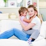 madre con hija sentada en el sofá — Foto de Stock