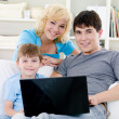 Happy family with son and laptop at home — Стоковая фотография