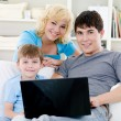 Happy family with son and laptop at home — Stockfoto