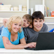 Smiling family using laptop - Stock Photo