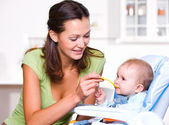 Mother feeding hungry baby — Stock Photo