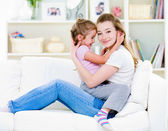 Mother with daughter sitting on the sofa — Stock Photo