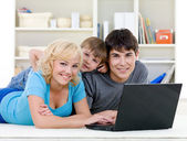 Smiling family using laptop — Stock Photo