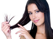 Smiling woman holding ends of her long hair — Stock Photo
