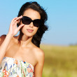 Beautiful woman on nature in black sunglasses — Stock Photo #3840373