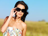 Beautiful woman on nature in black sunglasses — Stock Photo