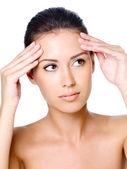 Woman stroking forehead — Stock Photo
