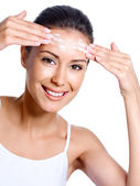 Happy woman applying cream on her forehead — Stock Photo