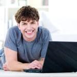 Smiling guy typing on laptop — Stock Photo