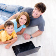 High-angle portait of family with laptop - Stock Photo