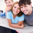 familia feliz sonriente con el ordenador portátil — Foto de Stock