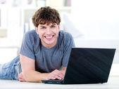 Smiling guy typing on laptop — Stock Photo
