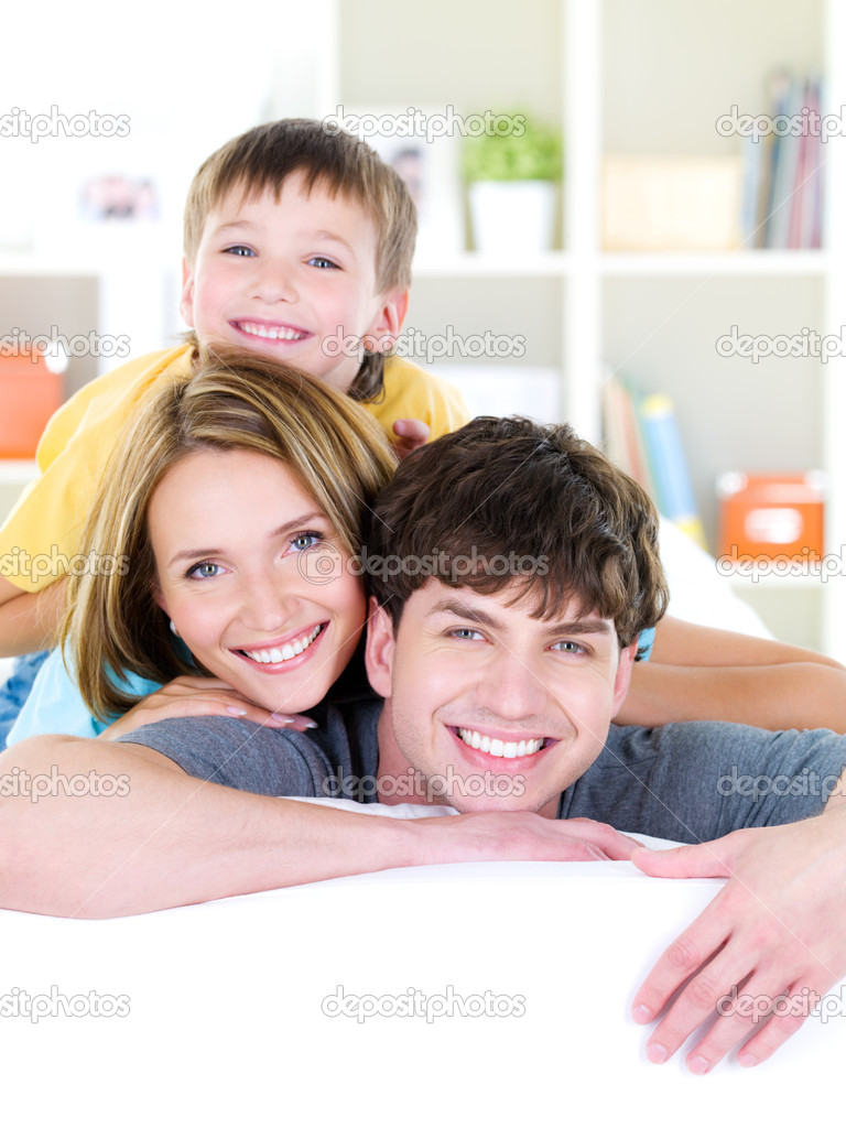 Close-up happy smiling faces of young family of three with son - indoors — Stock Photo #3890448