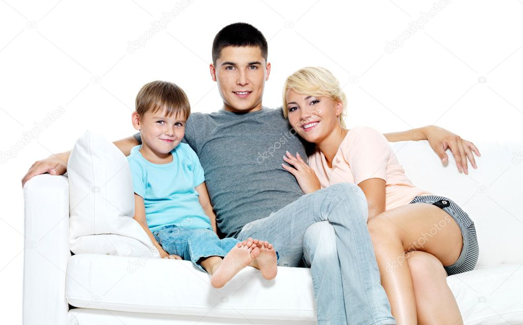 Happy young smiling family with kid sitting on white sofa - Isolated — Stock Photo #3907129