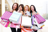 Happy smiling women with shopping bags — Stock Photo