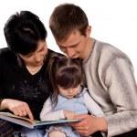 Happy family reading a book — Stock Photo