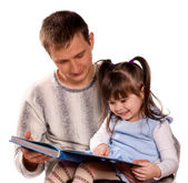 Happy family reading a book — Stockfoto