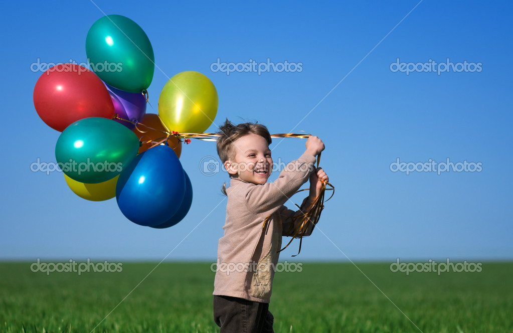 Happy child with balloons running on the spring field — Stock Photo #3016328