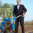 Royalty-Free Stock Photo: The businessman behind a tractor.