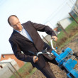 The businessman behind a tractor. — Stock Photo