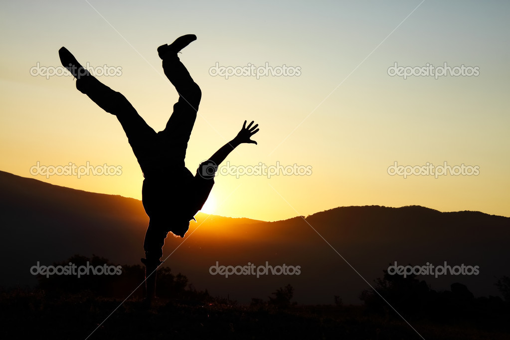 Happy man in mountains stay head over heels on one hand   Stock Photo #3286346