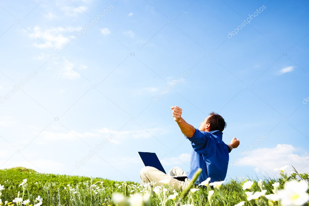 Man working with laptop in a meadow of flowers with copyspace  — Stock fotografie #3286361