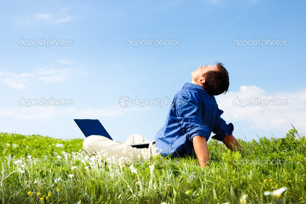 Man working with laptop in a meadow of flowers with copyspace  — Stock Photo #3286369