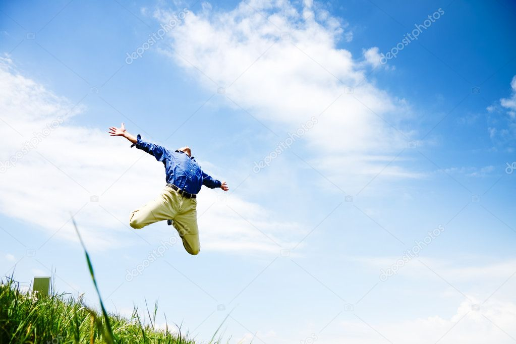 Businessman jumping on a green meadow with copyspace   Stock Photo #3286375