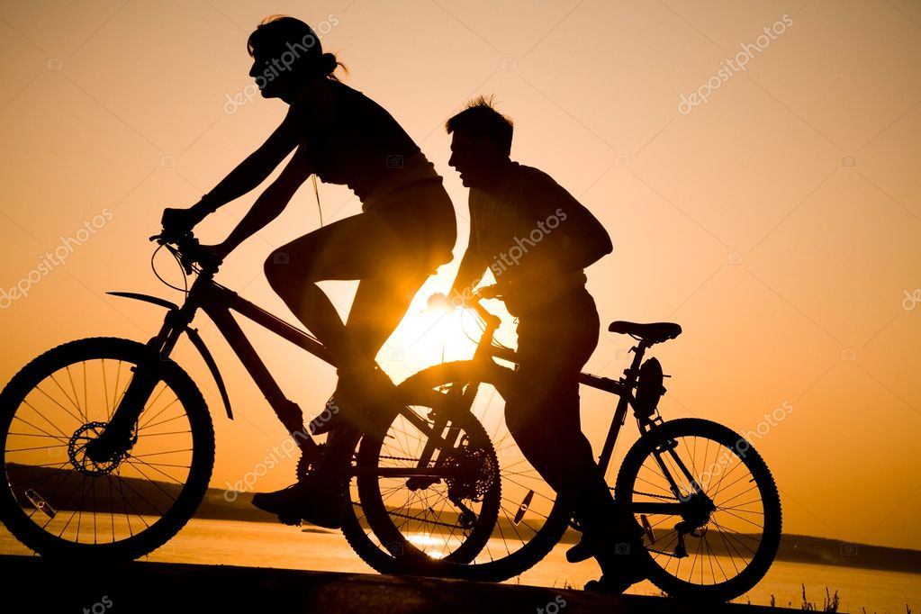 Image of sporty couple on bicycles outdoors against sunset. Silhouette. — Stock Photo #2840609