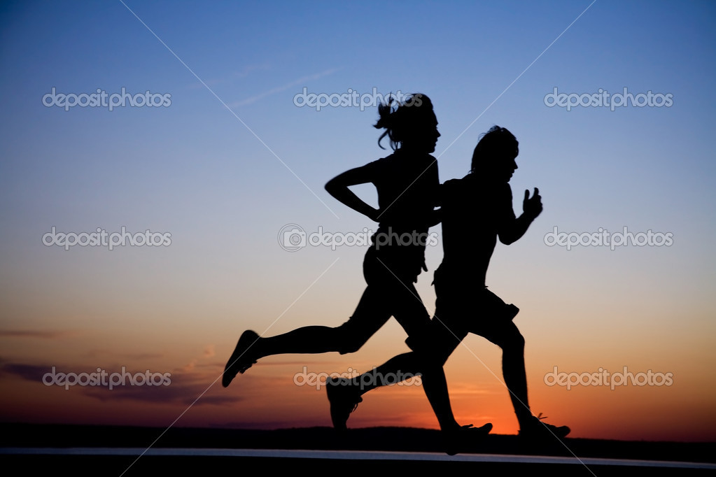 Young couple: man and  woman run together on a sunset on lake coast.  Silhouette. — Stok fotoğraf #2840618