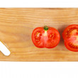 Cut tomato on kitchen board . — Stock Photo