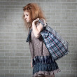 Tired redhaired woman with shopping bag. — Stock Photo #3419435
