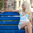 Happy young woman sit on the bench — Stock Photo