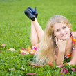Woman lying on a green grass — Stockfoto