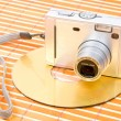 Compact digital camera and dvd disk - Stock Photo