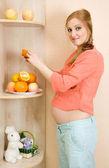 Donna incinta mangiando frutta — Foto Stock