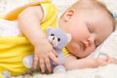 Baby sleeping with her bear toy — Stock Photo