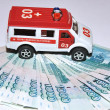Toy car ambulance and money — Stock Photo