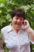 En äldre kvinna på naturen talar via telefon — Stockfoto