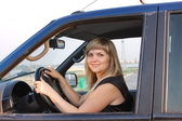Girl after the helm of car — Stock Photo