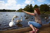 Girl feeding birds in a lake — Stock Photo
