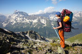 Hiker girl with backpack and ice-axe — Stock Photo