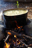 Kettle with food on campfire — Stock Photo