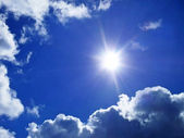 Blue sky with clouds and sunlight rays — Stock Photo