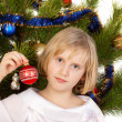 Nice girl decorates a Christmas tree — Stok fotoğraf