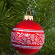 Red ornament christmas ball in a tree — Stock Photo